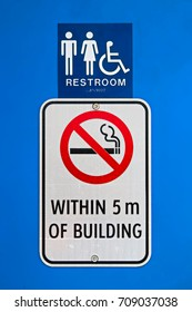 A no smoking within 5m of building sign at a reststop washroom.