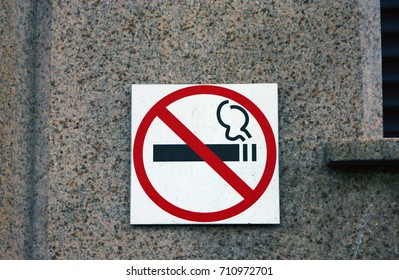 no smoling sign with strikeout black cigarette in red circle on white background on granite wall of building
