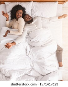 No space for two. Annoyed black wife angry to husband that sprawled out all over bed, lying down with arms and legs stretched out wide, top view