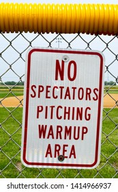 No spectator pitching warmup area sign on fence with baseball/ softball field in the background.