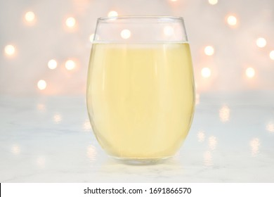 No Stem Wineglass mockup featuring a stemless wine glass filled with white wine. White lights glow romantically in the background.
