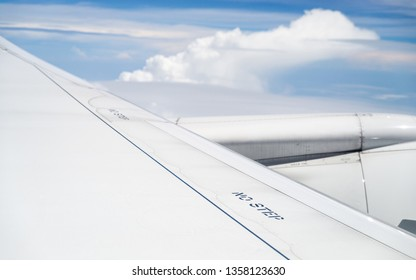 No step signs on commercial airplane wing, airplane in flight, shot through the window.