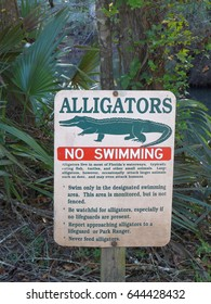 No Swimming caution sign in Florida Caverns State Park warns visitors of alligators in the waterways, and provides swimming rules.