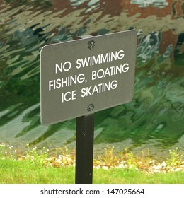No swimming fishing boating ice skating sign with wavy water in background
