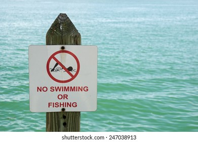 no swimming or fishing sign on a post with out of focus water behind it