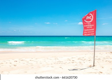 No Swimming Here !!! danger sign at the beach,on red flag in English and Thailand and China.