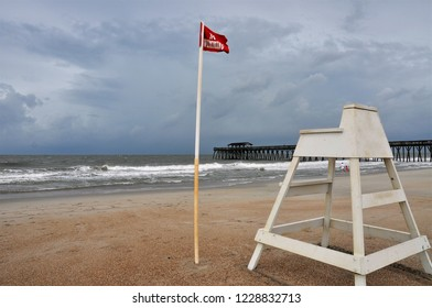 A no swimming red flag blows in the wind beside a lifeguard chair.