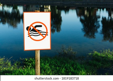 No swimming sign. Entering water is forbidden. Safety lake shore restrictions. Shallow water danger background. Small forest fishing pond.