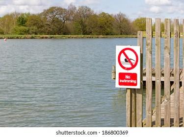 No swimming sign on jetty at edge of lake