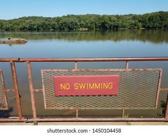 no swimming sign on metal fence with river
