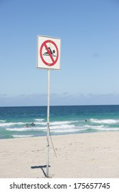 'No swimming' sign in the sharp foreground at beach, with surfer and swimmer on the ocean in the blurred background and with copy space.
