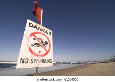 A no swimming warning sign on the beach at gold coast