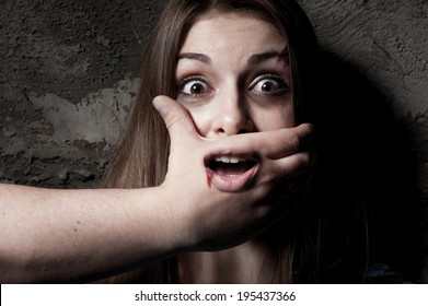 No! Terrified young woman with hand covering her mouth staring at camera