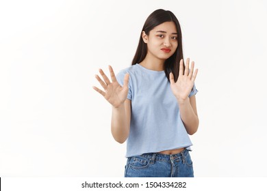 No thanks I pass. Indifferent asian reluctant girl refusing unintersting offer smirking displeased raise hands stop enough no gesture shaking palms refusal rejecting awful offer white background