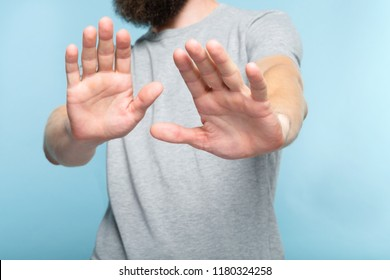 no thanks. rejection refusal and denial. man putting hands forward as if pushing smth away palms in foreground. cropped portrait of a bearded guy on blue background.