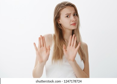 No I think refuse. Bothered displeased attractive popular female student showing rejection gesture with raised palms, waving in no answer as turning away, frowning awkward over gray background