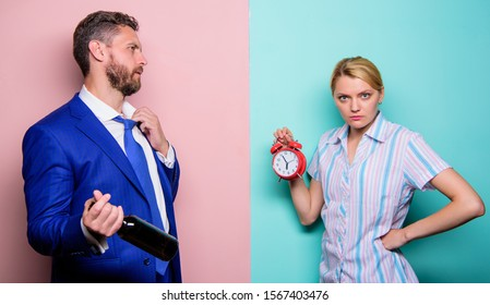 no time for jokes. problems in relationship. family psychology. unhappy life. man drink wine. woman show time on alarm clock. wife wondering why husband reveler came home so late. family routine.