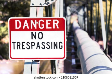No trespassing, high contrast danger sign by industrial pipeline.