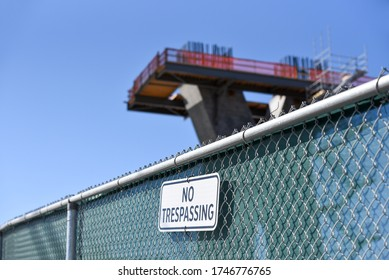 No trespassing sign at construction site with pillar for bridge in progress in background