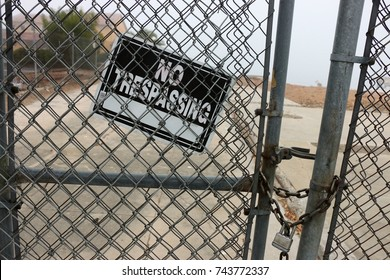 No Trespassing sign hangs on a rusted chain link fence with a padlock.