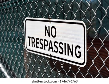 No trespassing sign on chain link fence at construction site