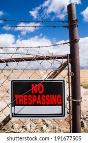 """The """"No Trespassing"""" sign on the rusty chain link fence."""