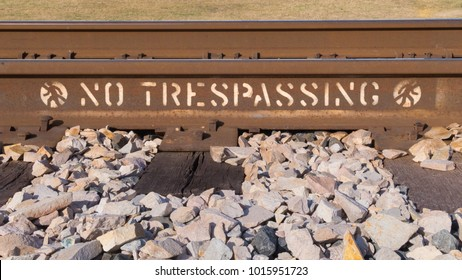 a no trespassing sign stensiled on the side of a rusted railroad track