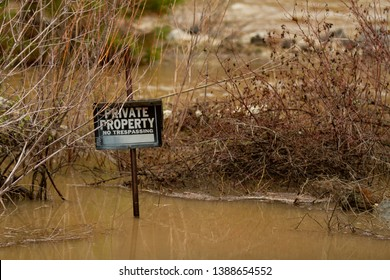 No trespassing sign that is being flooded with water