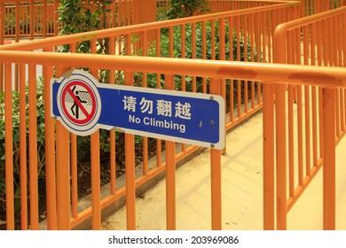 """No trespassing"" warning signs on yellow railing"