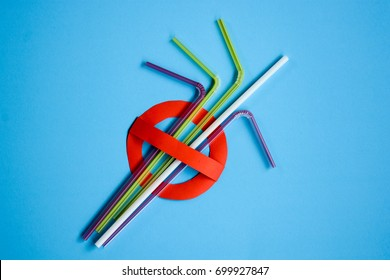 No use symbol in red with plastic straws and fork on blue background.  Plastic pollution is harmful to  marine lives including turtle, shark and whale. Environmental concept. Ban single use plastic.