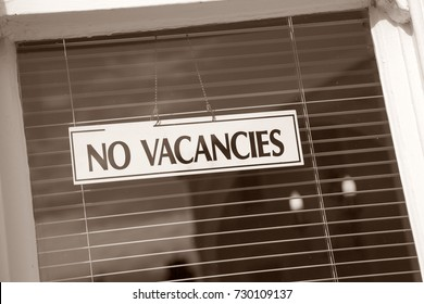 No Vacancies Hotel Sign on Window in Black and White Sepia Tone