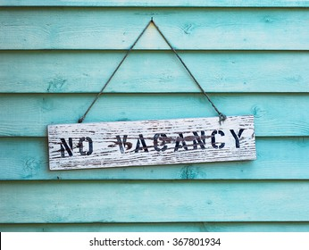 No Vacancy sign hanging on blue or aqua painted cedar siding.
