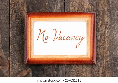 No Vacancy text in frame on wooden background