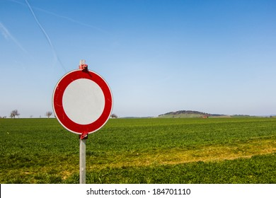 No vehicles traffic sign with green field and blue sky in the background. Selective focus