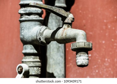 No water concept: old garden faucet not working, on red wall as background