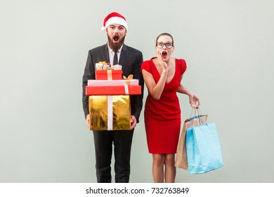 No way! Amazed bearded man in red hat and woman in red dress, holding christmas gifts and colorful packages and looking at camera with wonder face. Studio shot on gray background. Studio shot