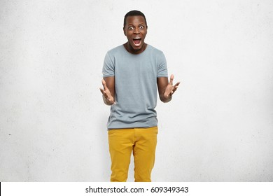 No way! Bug-eyed young dark-skinned male dressed casually having scared fearful look, screaming and gesturing actively with both hands, shocked with unexpected news. Human emotions and feelings