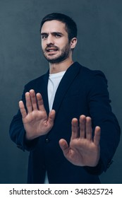 No way! Frustrated young man looking at camera and gesturing while standing against grey background