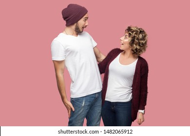 No way. Portrait of excited couple of friends in casual style standing and looking to each other with amazing faces, big eyes and toothy smile. Isolated, indoor, studio shot, pink background