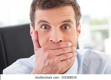 No way! Shocked young man in formal wear covering mouth with hand and looking at camera while sitting at his working place
