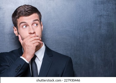 No way! Shocked young man in formalwear covering mouth with hand and looking away while standing against blackboard