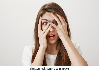 No words can describe her shock. Indoor shot of amazed beautiful european girl covering eyes with palms and peeking through fingers, dropping jaw while seeing amazing and awful things over gray wall