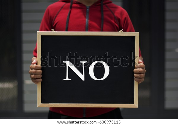 NO written on blackboard with someone is holding it