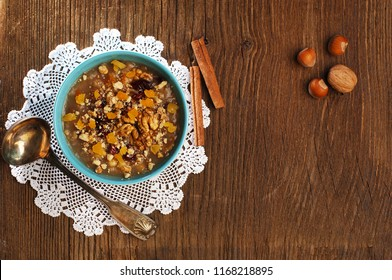 Noah's pudding in a blue bowl, ashure, wooden background, lace, silver ladle, walnut, hazelnuts, cinnamon sticks, top view, space, ashura