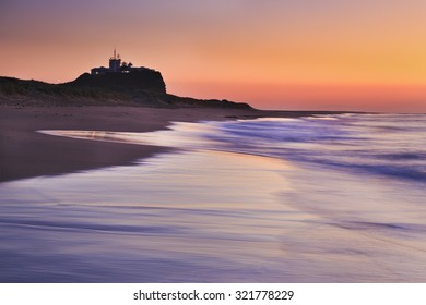 Nobbys lighthouse in Newcastle of Australia at sunrise sinking in warm pink rays of rising sun