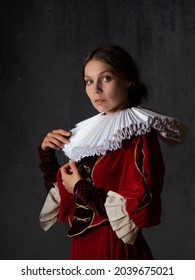 A noble lady in a luxurious red dress, medieval style, a young woman in a round Spanish collar, a portrait in the style of Renaissance paintings - Shutterstock ID 2039675021