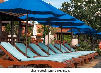 Nobody lounge chairs near swimming pool in hotel resort.