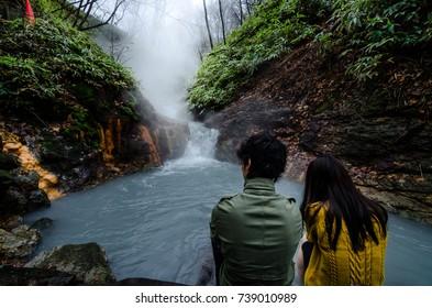 Noboribetsu, Japan- 15 NOV 2017: Beautiful couple soaking their leg in the natural footbath at the Oyunuma River, a hot spring river that flows from Lake Oyunuma, near hell valley, Noboribetsu