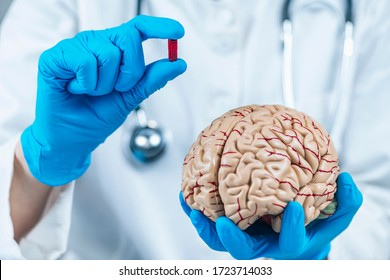 Nocebo Effect Concept. Female doctor holding model of brain and placebo supplement pill, explaining the placebo – nocebo effect phenomenon