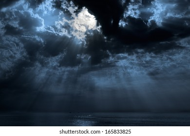 Nocturnal photo composition with moon, clouds, light beams and sea